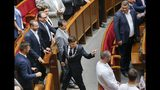In this photo taken on Monday, May 20, 2019, Ukrainian new President Volodymyr Zelenskiy, centre, leaves the parliament after his inauguration ceremony in Kiev, Ukraine. Ukrainian TV star Volodymyr Zelenskiy was sworn in as the country's new president on Monday, and promised to stop the war in the country's east against Russian-backed separatists and immediately disbanded parliament, which he has branded as a group only interested in self-enrichment. (AP Photo/Efrem Lukatsky)