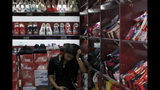 A worker browses her smartphone inside a shop selling shoes in Beijing, Thursday, May 23, 2019. An escalating trade war between the U.S. and China could mean higher prices on a broad array of products from toys to clothing. But some retailers will be less equipped to handle the pain than others, leaving consumers to carry the load. (AP Photo/Andy Wong)