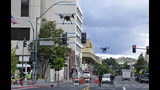 In this Tuesday, May 21, 2019 photo, two drones fly above Lake Street in downtown Reno, Nev., on, as part of a NASA simulation to test emerging technology that someday will be used to manage travel of hundreds of thousands of commercial, unmanned aerial vehicles (UAVs) delivering packages. It marked the first time such tests have been conducted in an urban setting. (AP Photo/Scott Sonner)