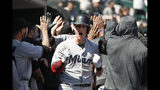 Miami Marlins' Garrett Cooper celebrates in the dugout after hitting grand slam in the ninth inning of a baseball game against the Detroit Tigers in Detroit, Thursday, May 23, 2019. (AP Photo/Paul Sancya)