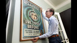 Kevin Kusinitz, a 63-year-old New Yorker who spent years being rejected from jobs for which he felt overqualified following an August 2012 layoff, straightens one of his old movie poster collection, in his apartment on New York's Upper East Side, Wednesday, May 22, 2019. About half of Americans think there's age discrimination in the workplace, according to a new poll by The Associated Press-NORC Center for Public Affairs Research. (AP Photo/Richard Drew)