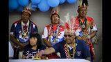 """La líder indígena maká Tsiweyenki, cuyo nombre en español es Gloria Elizeche (delante, izquierda), asiste a una ceremonia con Mateo Martínez (derecha) en la que el gobierno entregó títulos de propiedad a familias maká, con hombres vestidos con trajes tradicionales escoltándolos, en Mariano Roque Alonso, Paraguay, el 22 de abril de 2019. Tras la muerte del esposo de Tsiweyenki, que era el jefe de los maká, su viuda se convirtió en la primera mujer que hereda el puesto. """"A la viuda de Chemei se le consultan todos los asuntos; ella debe dar su aprobación o rechazo"""", explicó Martínez. (AP Foto/Jorge Saenz)"""