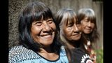 La líder indígena maká Tsiweyenki, cuyo nombre en español es Gloria Elizeche, sonríe junto a sus hermanas Cristina (centro) y Estela mientras cocinan en su patio, en Mariano Roque Alonso, Paraguay, el 29 de abril de 2019. Tras la muerte del esposo de Tsiweyenki, que era el jefe de los maká, su viuda se convirtió en la primera mujer en heredar el liderazgo de la tribu indígena. (AP Foto/Jorge Saenz)