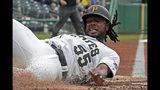 Josh Bells de los Piratas de Pittsburgh anota una carrera tras un doble de Melky Cabrera en el primer inning ante los Rockies de Colorado, el jueves 23 de mayo de 2019. (AP Foto/Gene J. Puskar)