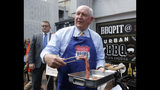 FILE - In this May 13, 2019, file photo, U.S. Secretary of Agriculture Sonny Perdue donning an apron prepares to barbecue U.S. beef in Tokyo. The U.S. Department of Agriculture estimates exports of U.S. beef and beef product could jump by up to $200 million a year, though they do face stiff competition from Australia and China. Japan still imposes limits on many farm products, seeking to guard its food security and politically important rural constituencies, and Perdue acknowledged that a broader trade deal with Tokyo may take time. (AP Photo/Yuri Kageyama, File)