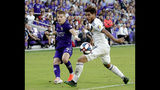Orlando City's Chris Mueller (9) takes a shot past LA Galaxy's Jonathan dos Santos during the first half of an MLS soccer match Friday, May 24, 2019, in Orlando, Fla. (AP Photo/John Raoux)