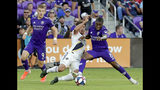 LA Galaxy's Jonathan dos Santos, center, and Orlando City's Jhegson Sebastian Mendez (8) battle for possession of the ball as forward Chris Mueller (9) watches during the first half of an MLS soccer match Friday, May 24, 2019, in Orlando, Fla. (AP Photo/John Raoux)