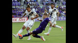 Orlando City's Chris Mueller (9) takes a shot against LA Galaxy's Rolf Feltscher (25) during the first half of an MLS soccer match Friday, May 24, 2019, in Orlando, Fla. (AP Photo/John Raoux)