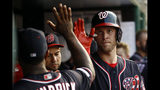 Washington Nationals' Kyle McGowin, right, high-fives teammate Howie Kendrick after scoring on Adam Eaton's groundout in the third inning of a baseball game against the Miami Marlins, Friday, May 24, 2019, in Washington. (AP Photo/Patrick Semansky)