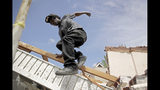 Tavaris McClain, left, jumps off a pile of debris as he cleans up outside his mother's destroyed home Thursday, May 23, 2019 after a tornado tore though Jefferson City, Mo. late Wednesday. (AP Photo/Charlie Riedel)
