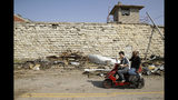 People ride a motor scooter past tornado debris along a wall of the former Missouri State Penitentiary Thursday, May 23, 2019 after a tornado tore though Jefferson City, Mo., late Wednesday. (AP Photo/Charlie Riedel)