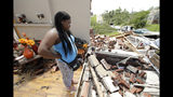 Iesha McClain looks through her destroyed home Thursday, May 23, 2019 after a tornado tore though Jefferson City, Mo. late Wednesday. (AP Photo/Charlie Riedel)