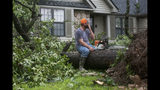 Homeowner Jason Waldon wipes away sweat while taking a break with his chainsaw in the Briarbrook neighborhood of Carl Junction, Mo., on Thursday, May 23, 2019. A tornado damaged the area on Wednesday evening, but no fatalities were reported. The National Weather Service says a deadly storm in southeast Kansas and southwest Missouri spawned four tornadoes in roughly 50 miles. (Roger Nomer/The Joplin Globe via AP)