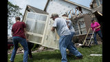 Keith James, center, hurries to move a cabinet out of his house before the roof collapses in the Briarbrook neighborhood of Carl Junction, Mo., on Thursday, May 23, 2019. The National Weather Service says a deadly storm in southeast Kansas and southwest Missouri spawned four tornadoes in roughly 50 miles. Weather Service Meteorologist Mark Burchfield in Springfield, Mo., said Thursday that two of the tornadoes Wednesday night were EF3 tornadoes, including one in Carl Junction, with winds of 140 mph. (Roger Nomer/The Joplin Globe via AP)