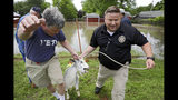 John DesBarres, left, and Tulsa County Undersheriff George Brown rescue one of DesBarres goats as flood waters rise in the Town and Country Neighborhood in Sand Springs, Okla., Thursday, May 23, 2019. (Mike Simons/Tulsa World via AP)