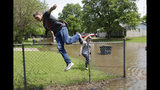 Chase Burgoon jumps a fence to get to his home as floodwaters approach in the Meadow Valley neighborhood in Sand Springs, Okla., Thursday, May 23, 2019. At right is his girlfriend Sierra Cooper. (Mike Simons/Tulsa World via AP)