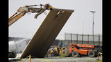 FILE - In this Feb. 27, 2019, file photo, a border wall prototype falls during demolition at the border between Tijuana, Mexico, and San Diego. The government is demolishing eight prototypes of Donald Trump's prized border wall that instantly became powerful symbols of his presidency when they were built nine months after he took office. U.S. District Judge Haywood Gilliam Jr. has blocked President Donald Trump from building sections of his long-sought border wall with money secured under his declaration of a national emergency, Friday, May 24, 2019. (AP Photo/Gregory Bull, File)