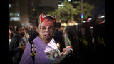 A woman wears a retouched mask with the image of Brazil's President Jair Bolsonaro during a protest against education cuts in Sao Paulo, Brazil, Thursday, May 23, 2019. A few hundred students demonstrated in Rio de Janeiro and Sao Paulo to protest big cuts in federal funding for the public education network by President Jair Bolsonaro.(AP Photo/Victor R. Caivano)