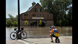 Andy Gaul of Tucson, Arizona photographs his bike in front of the flooded Lewis & Clark Boat House and Museum in Frontier Park on Friday, May 24, 2019. St. Charles officials closed the park and the Katy Trail due to Missouri River flooding, moving a weekend Irish Fest to New Town St. Charles. (Robert Cohen/St. Louis Post-Dispatch via AP)