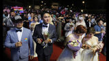 Taiwanese same-sex couples walk thered carpet at their wedding party in Taipei, Taiwan, Saturday, May 25, 2019. Taiwan became the first place in Asia to allow same-sex marriage last week. Hundreds of same-sex couples in Taiwan rushed to get married Friday, the first day a landmark decision that legalized same-sex marriage took effect. (AP Photo/Chiang Ying-ying)