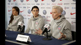 United States women's national soccer team members, from left, Carli Lloyd and Alex Morgan listen as teammate Megan Rapinoe speak to reporters during a news conference in New York, Friday, May 24, 2019. (AP Photo/Seth Wenig)