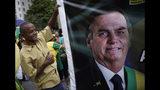 Un partidario del presidente brasileño Jair Bolsonaro ayuda a cargar una imagen gigante del mandatario durante una marcha en apoyo a él, en la playa de Copacabana en Río de Janeiro, Brasil, el domingo 26 de mayo de 2019. (AP Foto/Silvia Izquierdo)