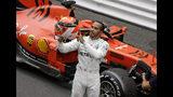 El piloto británico Lewis Hamilton, de la escudería Mercedes, señala el nombre de Niki Lauda en su casco, en un homenaje a la recién fallecida leyenda de la Fórmula Uno, después de ganar el Gran Premio de Mónaco, el domingo 26 de mayo de 2019. (AP Foto/Luca Bruno)