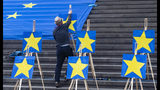 A man installs paintings of Europe Stars on stairs, during a demonstration of the 'Pulse of Europe' movement, in central Berlin, Sunday, May 27, 2019. The 2019 elections to the European Parliament will take place between May 23 and May 26. In Germany, the European election take place on Sunday, May 26, 2019. (Paul Zinken/dpa via AP)