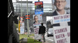 In this Thursday, May 16, 2019 photo, a man stands in fron of posters for the European and state elections of Social Democrats, SPD, and Alternative for Germany, AfD, in Bremerhaven, Germany. The city became a battleground for EU's fragile political center, support for Germany's Social Democrats has ebbed dramatically in recent years, but nowhere is their fate more closely watched than in the tiny city-state of Bremen. (AP Photo/Martin Meissner)