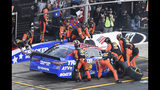 Crew members lift Martin Truex Jr.'s car to change a flat tire during a NASCAR Cup Series auto race at Charlotte Motor Speedway in Concord, N.C., Sunday, May 26, 2019. (AP Photo/Mike McCarn)