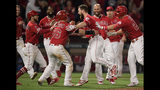 Los Angeles Angels' Jared Walsh, center right, celebrates with Kole Calhoun, center left, after Walsh hit a walk-off single during the ninth inning of the team's baseball game against the Texas Rangers on Saturday, May 25, 2019, in Anaheim, Calif. The Angels won 3-2. (AP Photo/Mark J. Terrill)