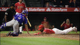 Los Angeles Angels' Luis Rengifo, right, scores on a double by Kole Calhoun as Texas Rangers catcher Isiah Kiner-Falefa reaches for a late tag during the ninth inning of a baseball game Saturday, May 25, 2019, in Anaheim, Calif. (AP Photo/Mark J. Terrill)