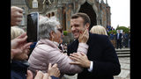 French President Emmanuel Macron smiles to a supporter after voting in the European parliamentary elections in Le Touquet, northern France, Sunday May 26, 2019. France is looking at an epic battle between pro-EU centrist President Emmanuel Macron and anti-immigration, far-right flagbearer Marine Le Pen in the European Parliament vote, a duel over Europe's basic values. (AP Photo/Kamil Zihnioglu)