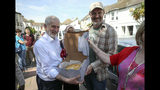 Labour Party leader Jeremy Corbyn, left, is gifted a spinach, asparagus and mushroom pie baked by local resident Gavin Williams who he met whilst out canvassing in Worthing, West Sussex, England, Wednesday, May 23, 2019 as voters head to the polls for the European Parliament election. Voters in Britain and the Netherlands are the first to cast their ballots in the four-day election for members of the European Parliament. (Andrew Matthews/PA via AP)