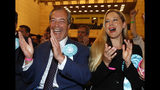 Brexit Party leader Nigel Farage, left, reacts as results are announced at the counting center for the European Elections for the South East England region, in Southampton, England, Sunday, May 26, 2019. (AP Photo/Alastair Grant)