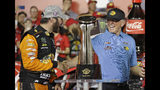 Martin Truex Jr., left, is congratulated by team owner Joe Gibbs in Victory Lane after winning the NASCAR Cup Series auto race at Charlotte Motor Speedway in Concord, N.C., Sunday, May 26, 2019. (AP Photo/Chuck Burton)