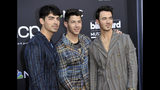 "FILE - This May 1, 2019 file photo shows Joe Jonas, from left, Nick Jonas and Kevin Jonas, of the Jonas Brothers, at the Billboard Music Awards in Las Vegas. The brothers have signed a deal with Macmillan to publish their memoir. The book will delve into the band's formation, rise to stardom, breakup in 2013 and reconciliation as a music group earlier this year. ""Blood"" will hit stores Nov. 12. (Photo by Richard Shotwell/Invision/AP, File)"