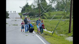 A family ducks under power lines as they make their way out of a tornado damaged neighborhood after being hit on Tuesday, May 28, 2019, south of Lawrence, Kan., near US-59 highway and N. 1000 Road. The past couple of weeks have seen unusually high tornado activity in the U.S., with no immediate end to the pattern in sight.(Chris Neal/The Topeka Capital-Journal via AP)