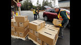 FILE - In this Monday, April 11, 2016 file photo, New Hampshire state and local officials load boxes of free bottled water in in Litchfield, N.H. New Hampshire is suing eight companies including 3M and Dupont for damage it says has been caused statewide by a class of potentially toxic chemicals found in everything from pizza boxes to fast-food wrappers. The state becomes the second in the nation to go after the makers of perfluoroalkyl and polyfluoroalkyl substances or PFAS and the first to target statewide contamination. (AP Photo/Jim Cole, File)