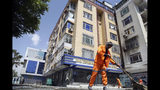 Municipality workers clean the site of explosions in Kabul, Afghanistan, Sunday, June 2, 2019. Afghan officials say there have been three explosions in the capital, Kabul, including a sticky bomb attached to a bus carrying university students. (AP Photo/Rahmat Gul)
