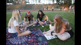 Paradise High School senior Brooke Grosvenor, right, signs a yearbook as she and her friends, Sierra Holt, from left, Tristin Reynolds and Kaylee Zuniga attend a gathering at the school's football field in Paradise, Calif., Wednesday, June 5, 2019. Many students of Paradise High lost their homes when the Camp Fire swept through the area and the school was forced to hold classes in Chico. (AP Photo/Rich Pedroncelli)