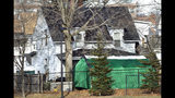 FILE - In this Jan. 17, 2017 file photo, a large green tent is seen in the back of a house on Hayward Street in Manchester, N.H., where authorities searched for clues in a missing person's case. New Hampshire authorities have identified three victims of Terry Peder Rasmussen, who is suspected of killing at least six women and children several decades ago, including his toddler daughter. Rasmussen, who used multiple names in many states, died in a California prison in 2010. (AP Photo/Elise Amendola, File)