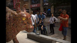 Visitors look at statues of bulls along a shopping street in Beijing, Friday, June 7, 2019. Asian shares were mostly higher Friday on investor optimism about a possible trade deal between the U.S. and Mexico before tariffs take effect. (AP Photo/Mark Schiefelbein)