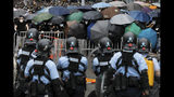Policemen in anti-riot gear stand watch as protesters use umbrellas to shield themselves near the Legislative Council in Hong Kong, Wednesday, June 12, 2019. Hundreds of protesters surrounded government headquarters in Hong Kong on Wednesday as the administration prepared to open debate on a highly controversial extradition law that would allow accused people to be sent to China for trial. (AP Photo/Vincent Yu)