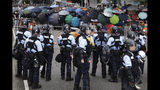 Policemen in anti-riot gear stand watch as protesters use umbrellas to shield themselves outside the Legislative Council in Hong Kong, Wednesday, June 12, 2019. Hundreds of protesters surrounded government headquarters in Hong Kong Wednesday as the administration prepared to open debate on a highly controversial extradition law that would allow accused people to be sent to China for trial. (AP Photo/Vincent Yu)