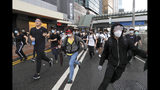 Protestors run near the Legislative Council in Hong Kong, Wednesday, June 12, 2019. Hundreds of protesters surrounded government headquarters in Hong Kong on Wednesday as the administration prepared to open debate on a highly controversial extradition law that would allow accused people to be sent to China for trial. (AP Photo/Kin Cheung)