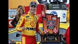Joey Logano stands with the trophy after winning a NASCAR Cup Series auto race at Michigan International Speedway, Monday, June 10, 2019, in Brooklyn, Mich. (AP Photo/Carlos Osorio)