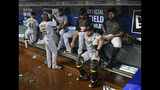 Pittsburgh Pirates players wait in the dugout during a rain delay called in the ninth inning of a baseball game against the Atlanta Braves, Tuesday June 11, 2019, in Atlanta. (AP Photo/John Amis)