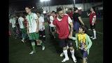 En esta foto del 27 de mayo de 2019, Daniel de Farias Viana abandona el campo con el hijo de su novia después de jugar un partido de fútbol con su equipo transexual BigTboys, en Rio de Janeiro, Brasil. (AP Foto / Silvia Izquierdo)