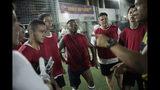 En esta foto del 27 de mayo de 2019, el jugador de fútbol masculino transgénero de Bigtboys Bruno dos Santos, en el centro, y sus compañeros de equipo escuchan a su entrenador durante un juego contra los Alligaytors, un equipo de hombres gays en Rio de Janeiro, Brasil. (AP Foto / Silvia Izquierdo)